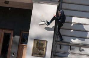 An anti-government protester kicks a surveillance camera during clashes with police in Sarajevo
