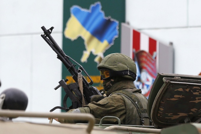 An armed serviceman looks out from a Russian army vehicle outside a Ukrainian border guard post in the Crimean town of Balaclava