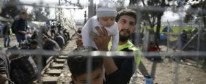 A migrant holds up a baby as he looks towards Macedonia through the Greek-Macedonian border fence, near the Greek village of Idomenii March 1, 2016. Macedonian police fired teargas to disperse hundreds of migrants who stormed the border from Greece on Monday as a deeply divided Europe traded barbs over the biggest humanitarian crisis in decades. As frustrations boiled over at restrictions imposed on people moving through the Balkans, migrants trapped on the Greece-Macedonia border tore down a metal gate in the barbed wire fence. REUTERS/Marko Djurica